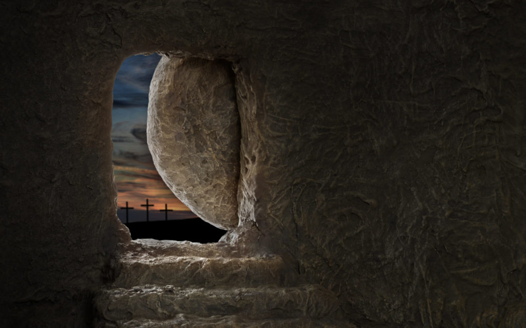 Empty tomb of Jesus with crosses in far hill